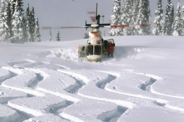 A helicopter picking up skiers on a heli-ski holiday