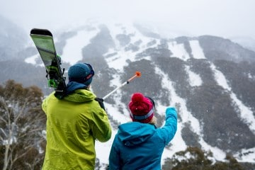 Skiers pointing at Thredbo Mountain in Australia
